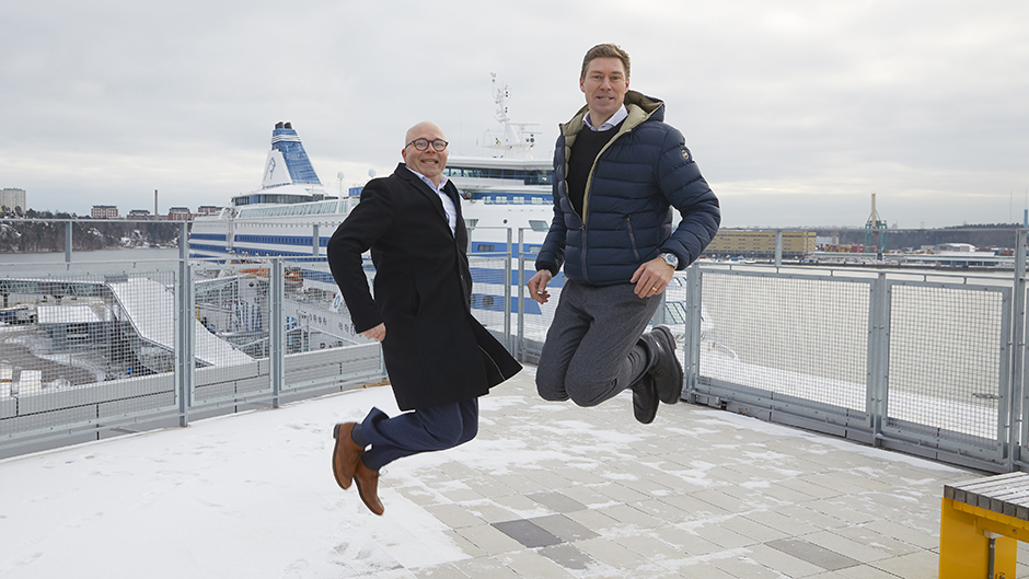 Johan Wallén and Stefan Scheja doing i jump in front of one of Tallink Silja´s vessels
