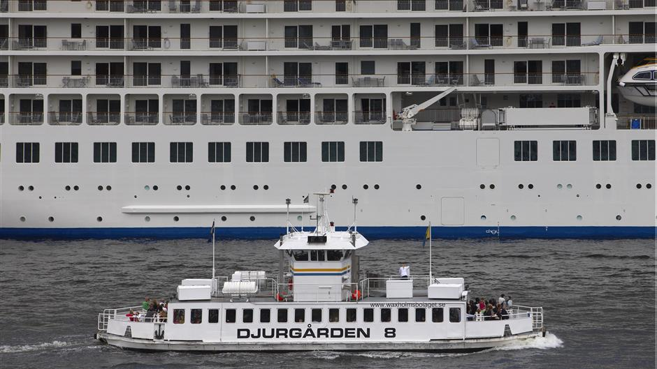 Small archipelago vessel passes large cruise vessel